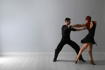 Beautiful young couple dancing near light wall. Space for text