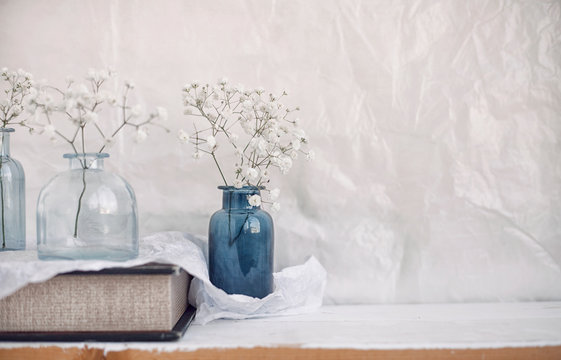 small vases with airy flowers on a shelf at home