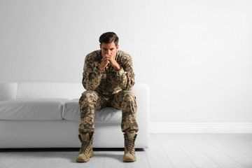Stressed military officer sitting on sofa near white wall indoors. Space for text