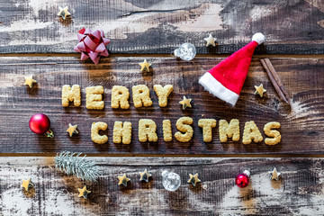 Merry Christmas written with cookies and Christmas decorations on wooden surface