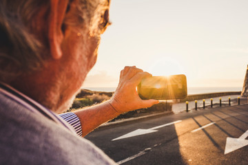 Senior man using smartphone and taking a picture at sunset, Tenerife