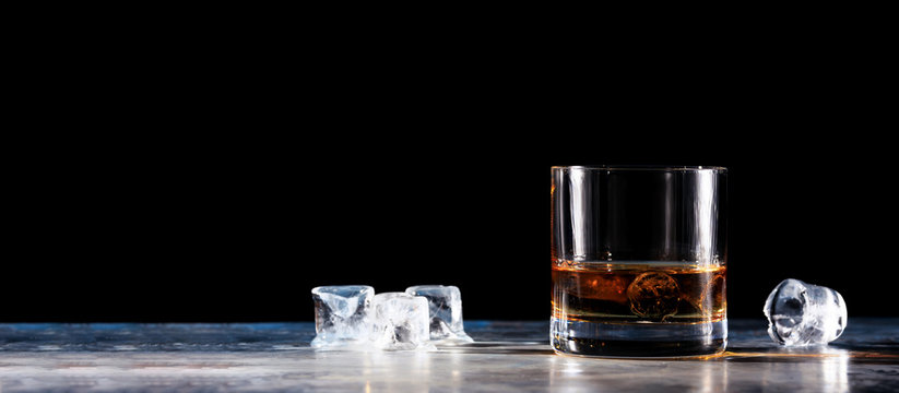 Glass of whiskey on the rocks with some ice on the table. Concept of hard liquor. Horizontal, wide screen banner format, isolated on black
