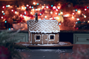 Gingerbread house sprinkled with icing sugar like snow. The spirit of Christmas. Garland on the background