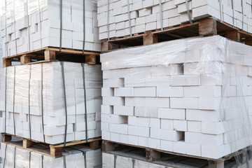 Pallets with white bricks outdoors. Building materials wholesale