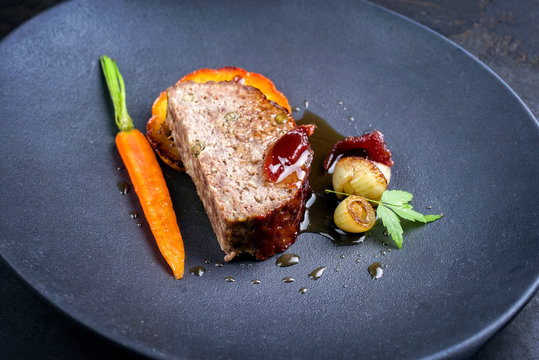 Minimalistic gourmet meatloaf slice with vegetable, quince and pumpkin as closeup on a modern design cast iron plate
