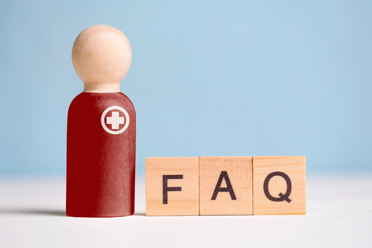 Abstract doctor with a medicine and an inscription: answers to popular questions - FAQ. A wooden figurine with cubes on a blue phone.