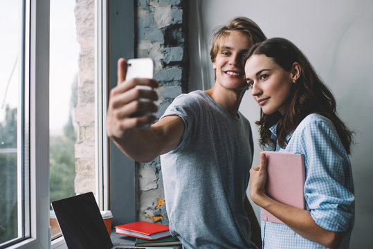 Caucasian male and female friends clicking selfie pictures for sharing to social networks using front smartphone camera indoors, teenage hipster influencers shooting video vlog via mobile phone