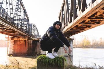 portrait of young rapper posing under a metal bridge