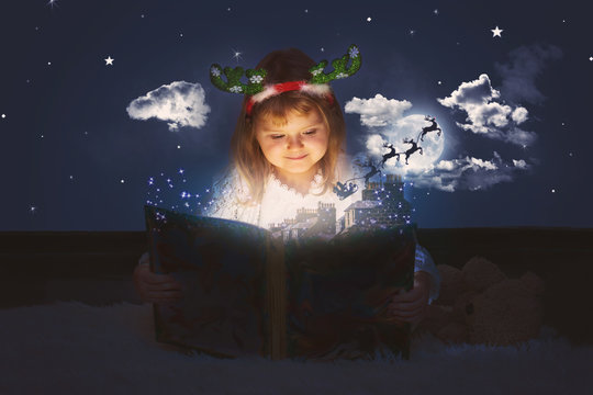 Little girl is reading magic book; Santa sleigh flying over roofs and towards night sky; Christmas magic and tales, background with copy space