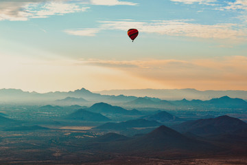 Poster de jardin Montgolfière / Dirigeable Hot Air Balloon floating over the Misty Mountains of the Arizona Desert near Phoenix