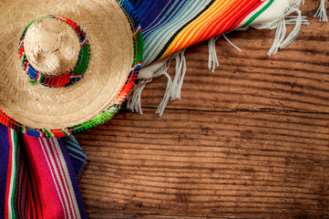 Celebrating Cinco de Mayo and Mexican fiesta conceptual idea with authentic hat (sombrero) and traditional colourful rug (serape) on wood background with copy space Wall mural