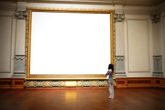 Woman with folded arms standing in front of and looking at big blank painting canvas with huge frame with negative area for your art and text.