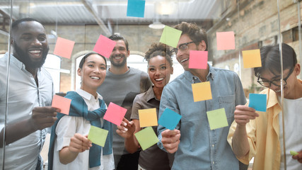 Working on business project together. Group of young and positive coworkers putting colorful sticky notes on a glass window in the creative office Wall mural