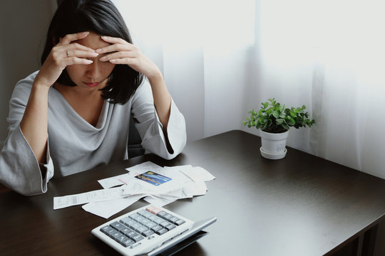 Asian woman pressing 2 hands on forehead with feeling stress, unhappy, worry and watching to receipt, slip, report or statement to prepare money for payment to burden of over shopping by credit card