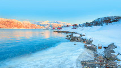 Panoramic view at fjord with coast of the Norwegian sea in the background snowy mountains at sunset - Snowy winter in the Arctic Circle - Tromso, Norway