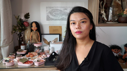 Singaporean artist Qixuan Lim poses next to cans containing tiny cherubic fetus heads, arms and legs or other human body parts, which she sculpted using clay and cosmetic paint, in Singapore