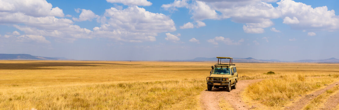 Safari tourists on game drive with Jeep car in Serengeti National Park in beautiful landscape scenery, Tanzania, Africa