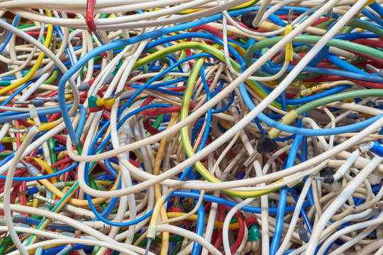 The bunch of electric wires of different colors are very much intertwined. On tangled wires is wire-end ferrules and markings. Chaos, confusion, tangle. Abstract background.