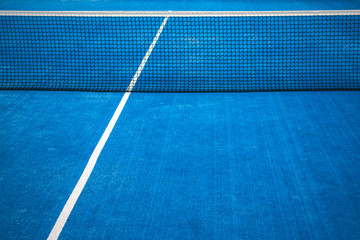 Blue paddle tennis net and court field background