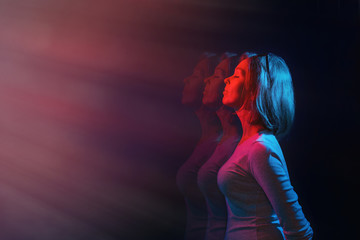 The concept of psychology and perception. The woman stands in profile, eyes closed, against a black background. Blue and red light. Copy space