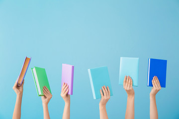 Female hands with books on color background
