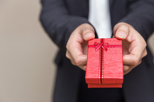 Hand giving present gift box reward in business office with space for text.