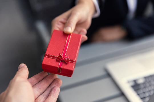 Business boss giving present gift box to office staff partner for job bonus concept.