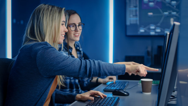 Two Female IT Programers Working on Desktop Computer in Data Center System Control Room. Team of Young Professionals In Software and Hardware Development, Doing Coding