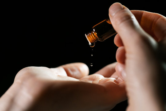 skin care and treatment - woman pouring oil in a hand from vial on black background