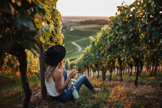 Young blonde woman relaxing in the vineyards in summer season. Girl sitting near the bottle and holding glass white wine. Outdoor farmer countryside style