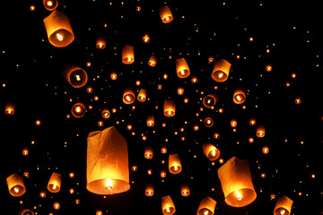 swarms of sky floating lanterns are launched into the air during New year's eve and Yee Peng lantern festival traditional at Chiang Mai , Thailand.