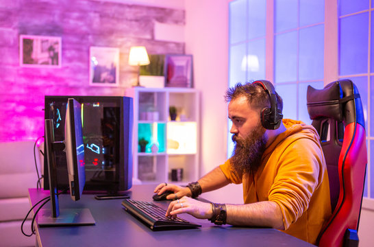 Concentrated bearded gamer looking at PC display