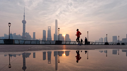 Silhouette morning runner running at famous bund zone with sun rising shanghai city background.