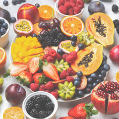 Wall Mural - Healthy rainbow fruit platter mango papaya strawberries oranges passion fruits berries on oval serving plate on white concrete kitchen top background, toned, selective focus