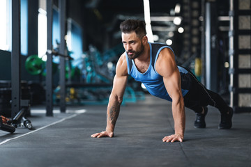 Wall Mural - Muscular athlete training on floor at gym