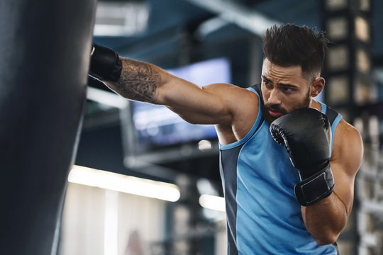 Sporty guy punching boxing bag at gym