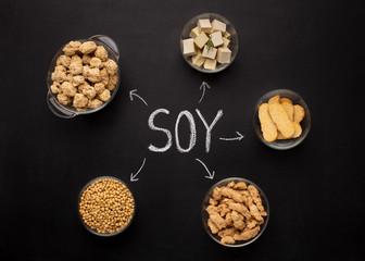 Fototapeta Soybeans, tofu, tempeh and soy meat on black chalkboard obraz
