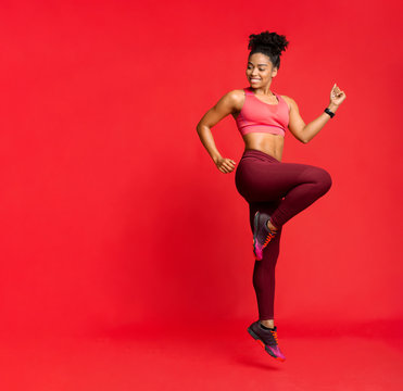 Joyful sporty african girl exercising, looking at free space