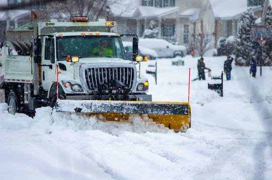 Front view of city services snow plow truck with yellow blade cleaning roads after winter storm with kids playing in the background