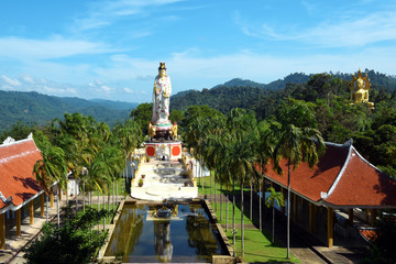 Wall Mural - panorama view to Wat Bang Riang temple in the jungle of Phang Nga province Thailand, with giant seated golden Buddha and large statue of Kwam Im (Guan Yin), the Chinese Goddess of Mercy