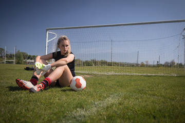 Female soccer player relaxing on field