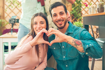 Closeup of couple making heart shape with hands..Beautiful young couple at outside is making heart sign with hands, smiling and looking at camera. Celebrating Saint Valentine's Day. Image
