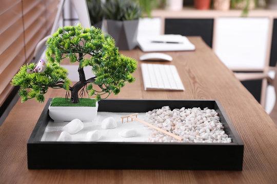 Beautiful miniature zen garden and computer on wooden table in office
