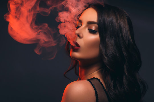 Glamour caucasian brunette woman in evening black dress on a neutral background. She pose sensually, blowing smoke from her mouth. Retro fashion mood.