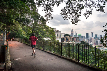 BOWEN ROAD, HONG KONG ISLAND - Sept 2013 - A jogger and a dog walker on Bowen Road, high above Hong Kong Island. The Central Plaza skyscraper can be seen in the background.