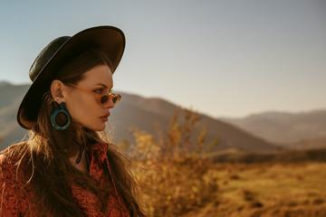 Outdoor close up fashion portrait of young beautiful confident brunette woman wearing stylish black wide brimmed hat, blue hoop earrings, orange dress, posing in mountain landscape. Copy, empty space