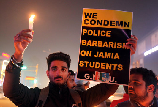 A demonstrator holding a candle and a placard attends a protest against a new citizenship law and to show solidarity with the students of New Delhi's Jamia Millia Islamia university, in Amritsar