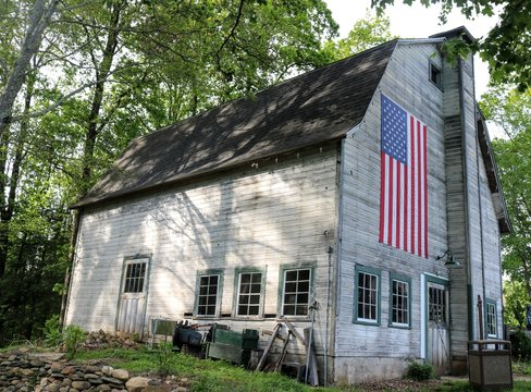 Old weathered wooden historic barn with American flag