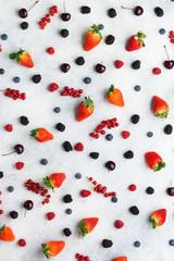 Wall Mural - Colorful berries background. Strawberries blueberries red currant blackberries raspberries, top view on white table, selective focus