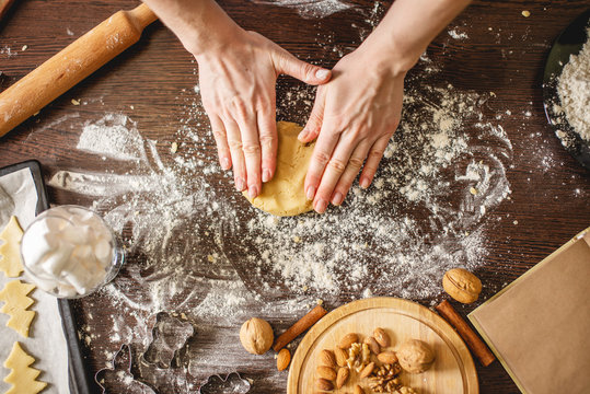 Cook housewife making cookies at home on a colorful kitchen. Woman rolls out the dough on a wooden table with flour